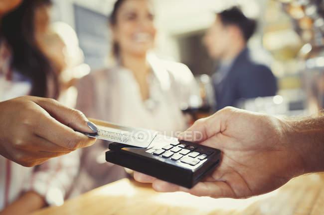 Frau mit Kreditkarte bezahlt Barkeeper mit kontaktlosem Bezahlen an Bar — Stockfoto