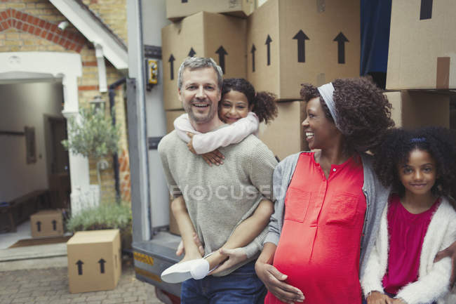 Portrait smiling pregnant multi-ethnic young family moving into new house — Stock Photo