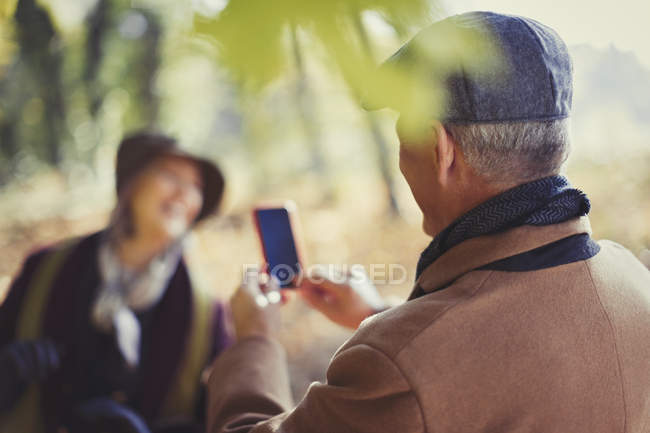 Senior man with camera phone photographing wife in park — Stock Photo