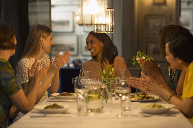 Smiling women friends dining and celebrating clapping at restaurant table — Stock Photo