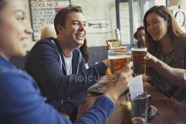 Amigos comemorando, brindando a copos de cerveja e vinho na mesa em bar — Fotografia de Stock