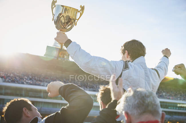 Formula one racing team carrying driver with trophy on shoulders, celebrating victory — стокове фото