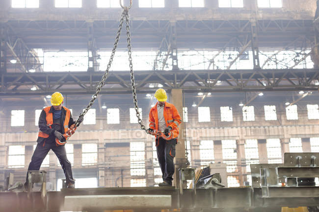 Steel workers with crane hooks in factory — Stock Photo