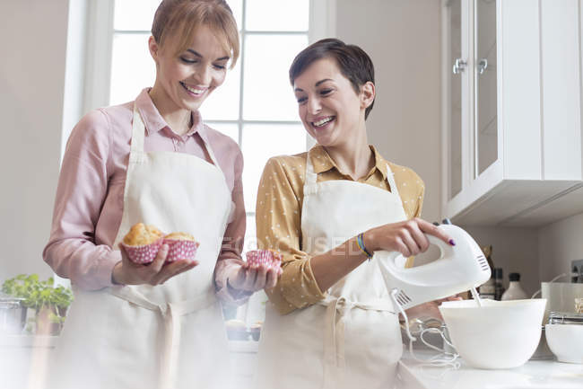 Des traiteuses souriantes préparent des muffins dans la cuisine — Photo de stock