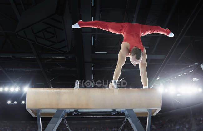 Male gymnast performing upside-down handstand on pommel horse in arena — Stock Photo