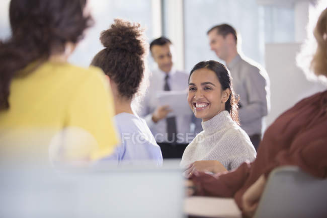 Smiling businesswoman talking to colleagues in conference audience — Stock Photo