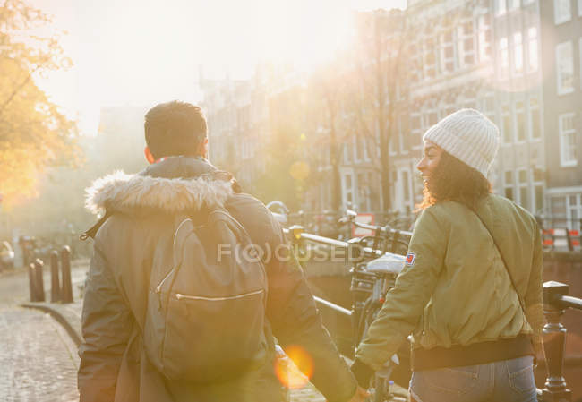 Young couple holding hands walking on sunny urban autumn street, Amsterdam — Stock Photo