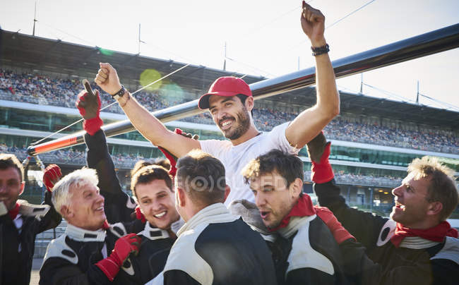 Formula one racing team carrying driver on shoulders, celebrating victory — Stock Photo