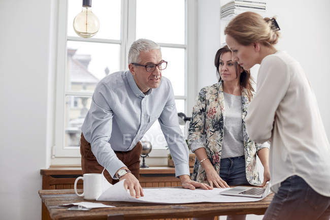 Architects reviewing, discussing blueprints in conference room meeting — Stock Photo