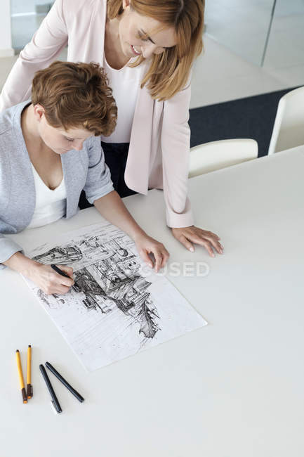 Female designers drawing sketch in conference room — Stock Photo