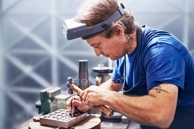 Focused jeweler using hammer in workshop — Stock Photo