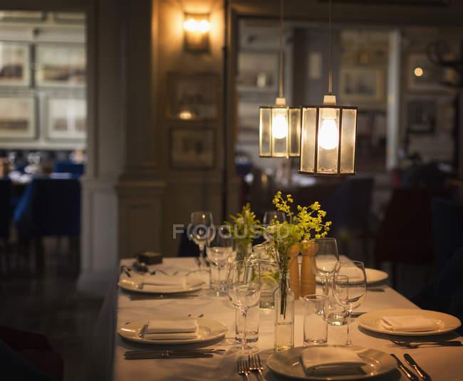 Illuminated pendant lights over placesettings on restaurant table — Stock Photo