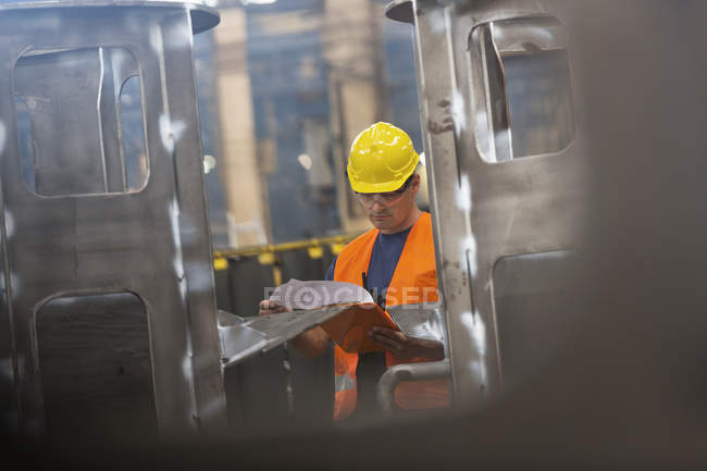 Steel worker reviewing paperwork in factory — Stock Photo