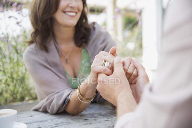Nahaufnahme zärtliches reifes Paar Händchen haltend am Terrassentisch — Stockfoto