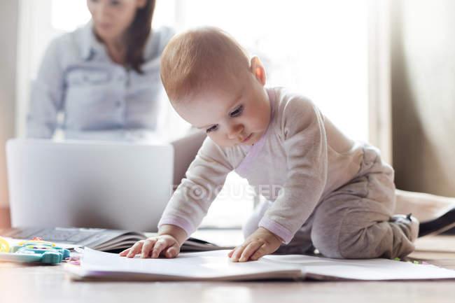 Bambina che gioca sul pavimento vicino alla madre che lavora sul computer portatile — Foto stock