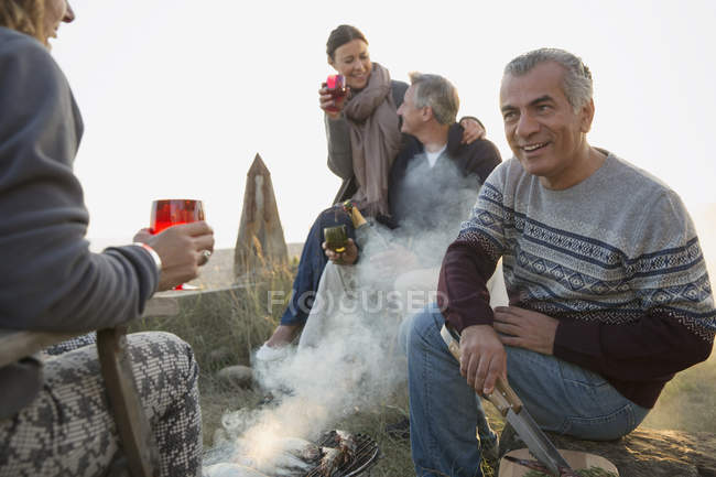Mature couples drinking wine and barbecuing on beach — Stock Photo