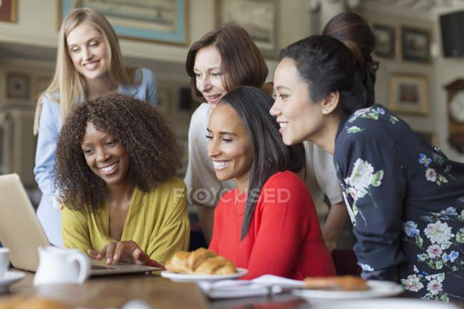 Donne amiche che utilizzano il computer portatile al tavolo del ristorante — Foto stock