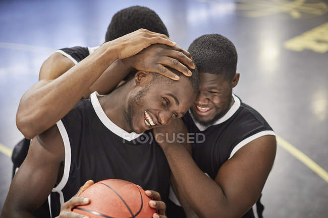 Happy young male basketball players hugging and celebrating after victory — Photo de stock
