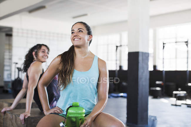Smiling young woman resting and drinking water post workout in gym — Stock Photo