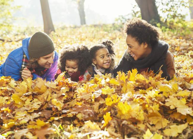 Verspielte junge Familie liegt im Herbstlaub in sonnigen Wäldern — Stockfoto