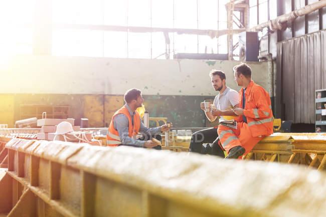 Steel workers enjoying lunch break in factory — Stock Photo