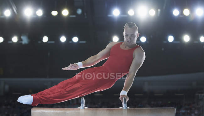 Male gymnast performing on pommel horse in arena — Stock Photo