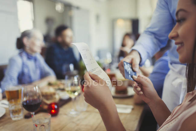 Woman reviewing bill and paying waiter with credit card at restaurant table — Stock Photo
