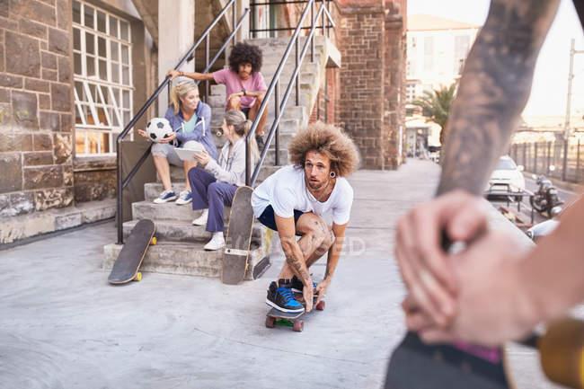 Amici lo skateboard e hanging out intorno urbani passi — Foto stock