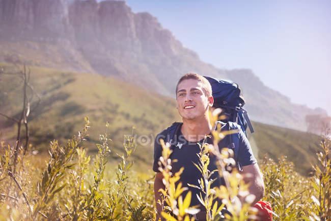 Giovane con lo zaino escursionismo in valle soleggiata — Foto stock