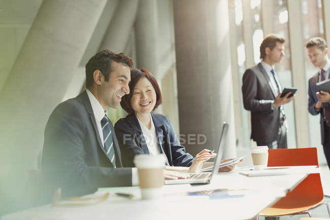 Businessman and businesswoman meeting working at laptop in conference room — Stock Photo