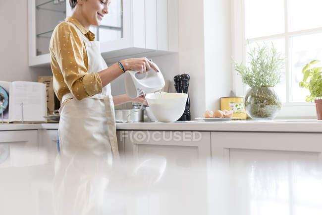 Femme cuisson, en utilisant un mélangeur électrique à main dans la cuisine — Photo de stock