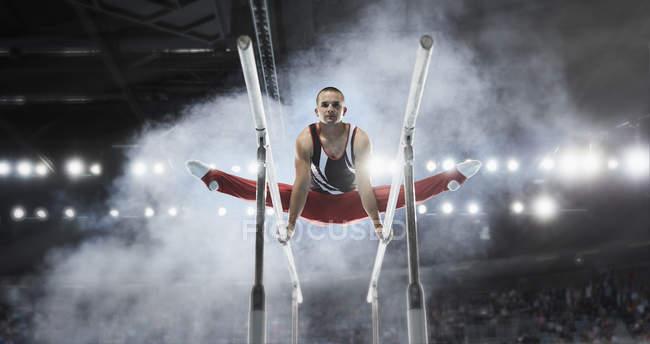 Concentré de gymnaste effectuant des scissions sur barres parallèles dans l'arène — Photo de stock