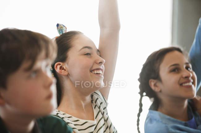 Lächelnd, eifrige Studentin eine Frage im Klassenzimmer — Stockfoto