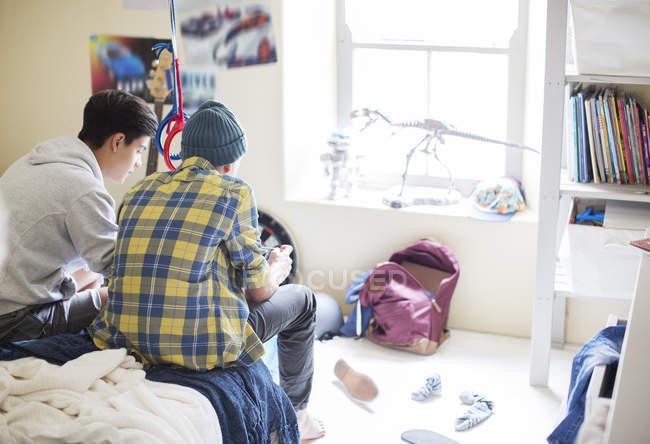 Deux adolescents, assis sur le lit dans la chambre malpropre — Photo de stock