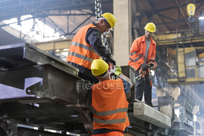 Steel workers fastening crane hook to steel in worker — Stock Photo