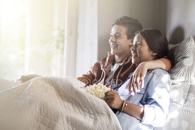 Couple d'adolescents couché dans son lit et regarder la télévision — Photo de stock