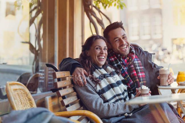 Portrait laughing young couple drinking milkshakes at urban sidewalk cafe — Stock Photo