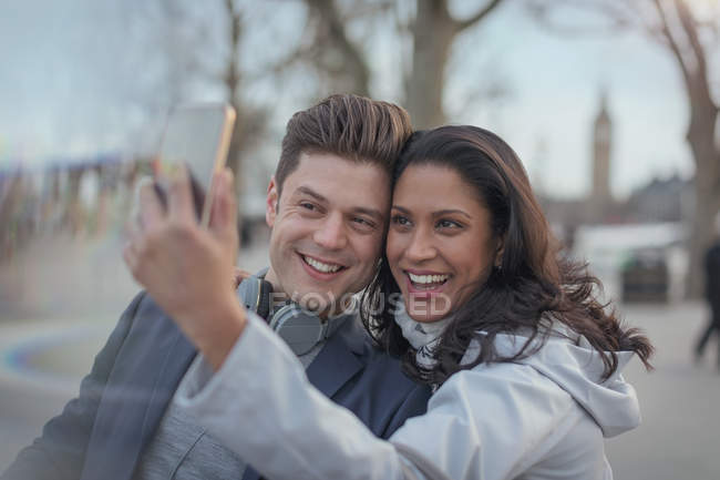 Smiling couple taking selfie with camera phone in urban park — Stock Photo
