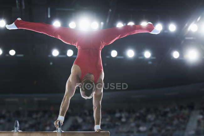 Male gymnast performing upside-down handstand on pommel horse — Stock Photo