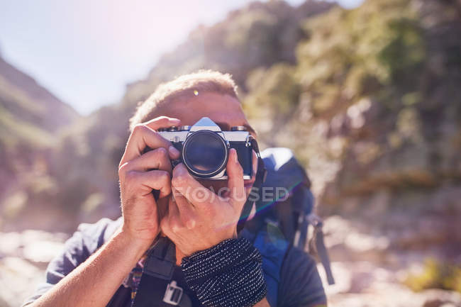 Young man hiking, photographing with camera — Stock Photo