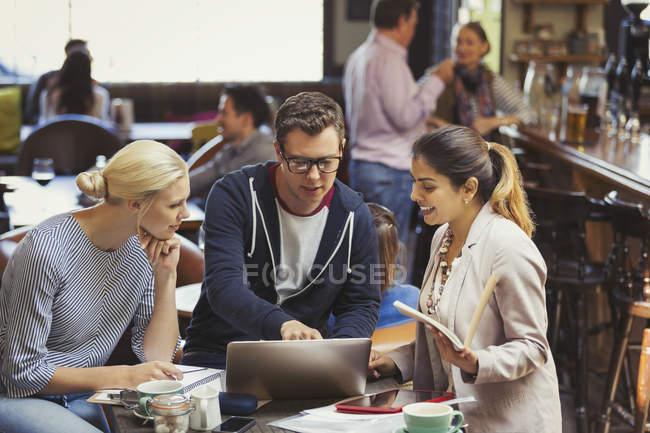 Empresarios creativos de reunión, utilizando la computadora portátil en café - foto de stock