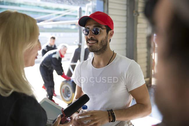 Feminino repórter de notícias entrevistando corrida masculina fórmula um motorista na garagem de reparação — Fotografia de Stock
