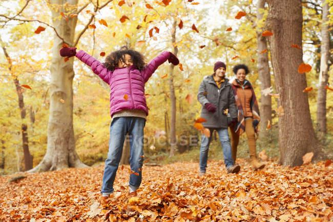 Chica juguetona lanzando hojas de otoño en el bosque - foto de stock