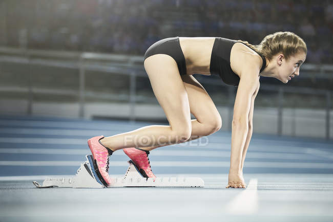 Side view of focused female runner ready at starting block on sports track — Stock Photo