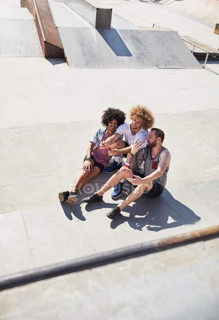 Vista aerea amici maschi scattare selfie con fotocamera telefono al parco skate soleggiato — Foto stock