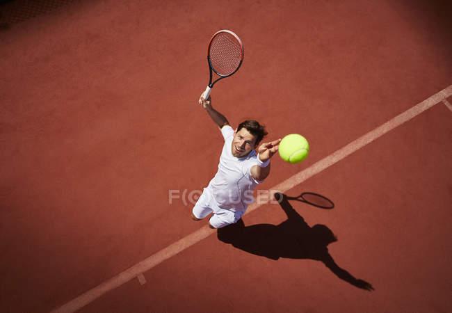 Вид зверху молоді чоловіки тенісист грати в теніс, яка виступає м'яч на Сонячний тенісний корт — стокове фото