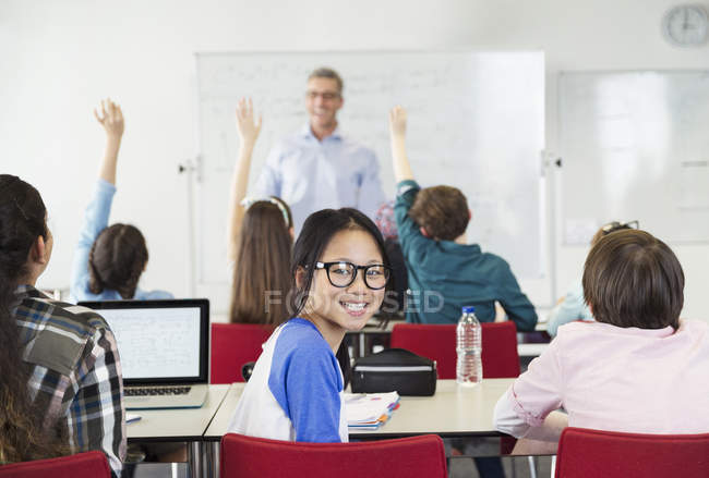 Portrait smiling girl student sitting in classroom during lesson — Stock Photo