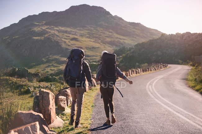 Jeune couple avec sacs à dos randonnée le long de la route ensoleillée et éloignée — Photo de stock