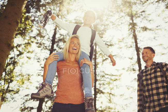 Mother carrying daughter on shoulders hiking in sunny woods — Stock Photo