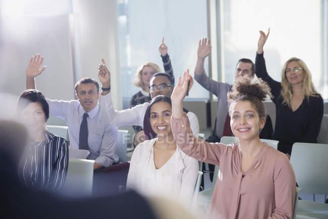 Улыбаясь деловых людей, задавая вопрос в аудитории конференции — стоковое фото